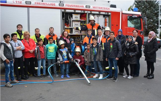 Flüchtlingskinder ließen sich jetzt von der Feuerwehr zeigen, wie mit Feuer umzugehen ist. Bei einem abschließenden Prüfung bekamen die Teilnehmer (im Bild mit den Feuerwehrlern und Vertretern der beteiligten Organisationen) ihre Zertifikate.